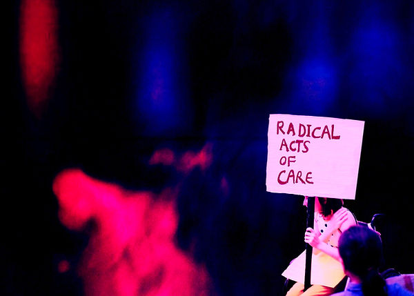 "A photo collage by Charlie Fitz. The background is an abstract cloudy image, with black, blue, red and pink throughout. At the front right if the image is a cut out photo if Charlie Fitz sitting in her wheelchair holding a protest placard which reads ""Radical Acts of Care."""