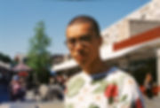 A young mixed race man stands centrally, only his upper half in the frame. He wears round tortoiseshell glasses and a tropical floral patterned jumper. He looks forward at the camera, squinting in the sunlight. In the background the shops of the Brunswick centre and a tall tree are out of focus and flats rise up behind. Above is a rich blue sky.
