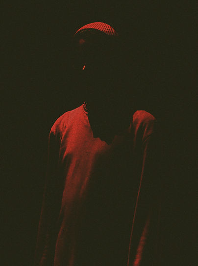 A figure bathed in red light and shadow stands in the centre frame, only their upper body is in frame. Their face is obscured in shadow, only the slight form of the ridge of their nose, their forehead and hat are discernible. They wear a long jumper. The photo has a red border.