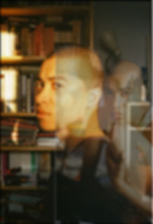 Two images are layered through one another, as if a double exposure both of Oscar a slender, mixed race man in his 20's with shaved hair. The image to the front is he is centre frame and sits half turned towards the camera, his face is half illuminated by the warm light of a sunset. He wears a dark blue t-shirt. Behind him is a bookcase brimming with books and magazines. The image behind and to the right is fainter than the first, he sits with his left knee bent and his head resting on top. His left arm clasps his knee. He stares into the camera. He wears a yellow vest.