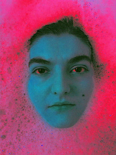 "Centre frame is the face of a ""white"" young woman surrounded by foamy water. On her left cheek she has a mole. The photo has been inverted so the water is a rich dark pink and the woman's face is blue with the corners of her eyes' red."