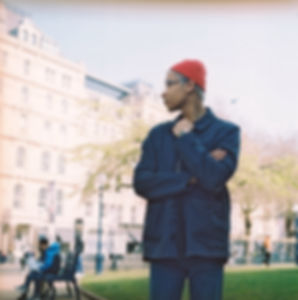 An off centre frame right stands a young mixed race man his lower legs cropped out of frame. His head is turned leftwards and his right arm holds his left, whilst his left hand is raised to the top of his blue jacket. He wears a small red beanie hat and blue jeans. In the background there is a stone building, grass, trees and a figure sat on a bench.