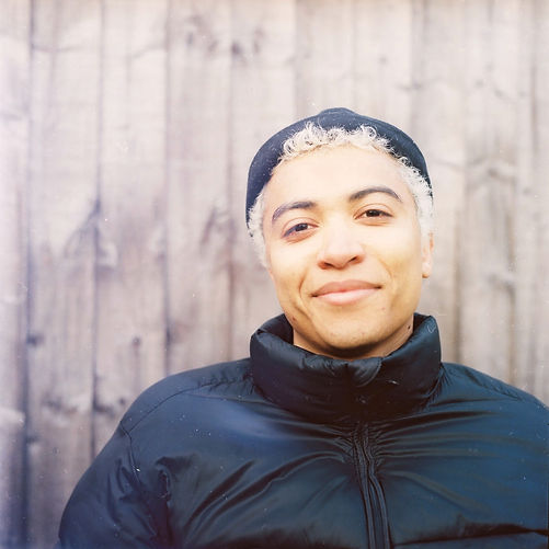 Off centre is the upper body of a young mixed race man who smiles at the camera. He wears a black hat and puffer coat and has bleached dyed blonde hair. Behind him are grey fence panels.