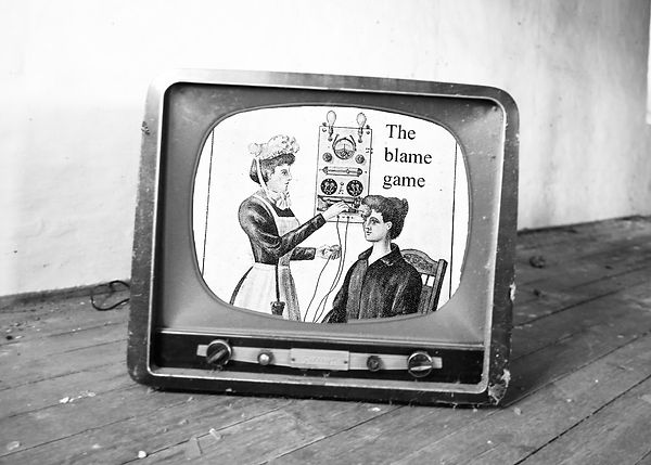 "A black and white photo collage by Charlie Fitz. There is a photo of a vintage television on a dusty wooden floor. There is a drawing om the tv of a nurse putting an electrode on a women's head. Above her head there is text which reads, ""The blame game""."