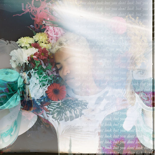 Centre frame a young mixed race man with bleached dyed blond hair wears a white jumper with a floral pattern on it, only his upper body in frame. His eyes are closed, he is lying down, seen from above and his head is surrounded by colourful flowers and paper decorations. A light leak runs vertically on the right side of the frame where there is also white text over-laying the image which reads: 'but you don't look sick' in a cursive font. Either side of the man is a partially transparent image of a mirrored figure of a white woman wearing a black top, black anti-pollution face mask and white and green neck-brace.