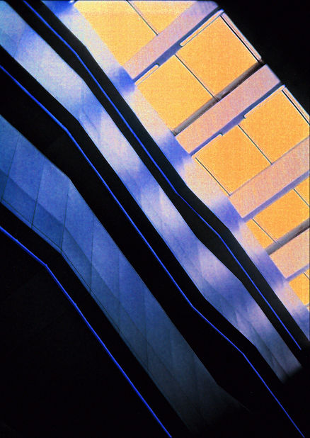 An inverted photograph showing three escalators side on ascending diagonally from right to left. The escalators are a shiny dark blue chrome and each has a fluorescent blue light stripe that runs the entirety of their length. On the upper right area of the frame there is a glass ceiling which is a pastel orange. The building is taken from the perspective of looking upwards towards the ceiling of the building.