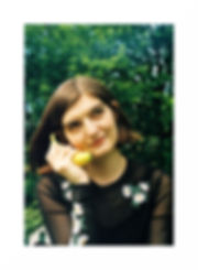 A photo of Charlie a white women in her twenties with chin length straight brown hair is holding a banana to her ear as though it is a phone. There is a green tree behin her, she is wearing a sheer, long sleeve black top with white flowers on.