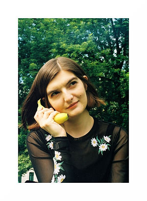 A photo of Charlie, a white woman in her twenties with chin length straight brown hair is holding a banana to her ear as though it is a phone. There is a green tree behind her, she is wearing a sheer, long sleeve black top with white flowers on.