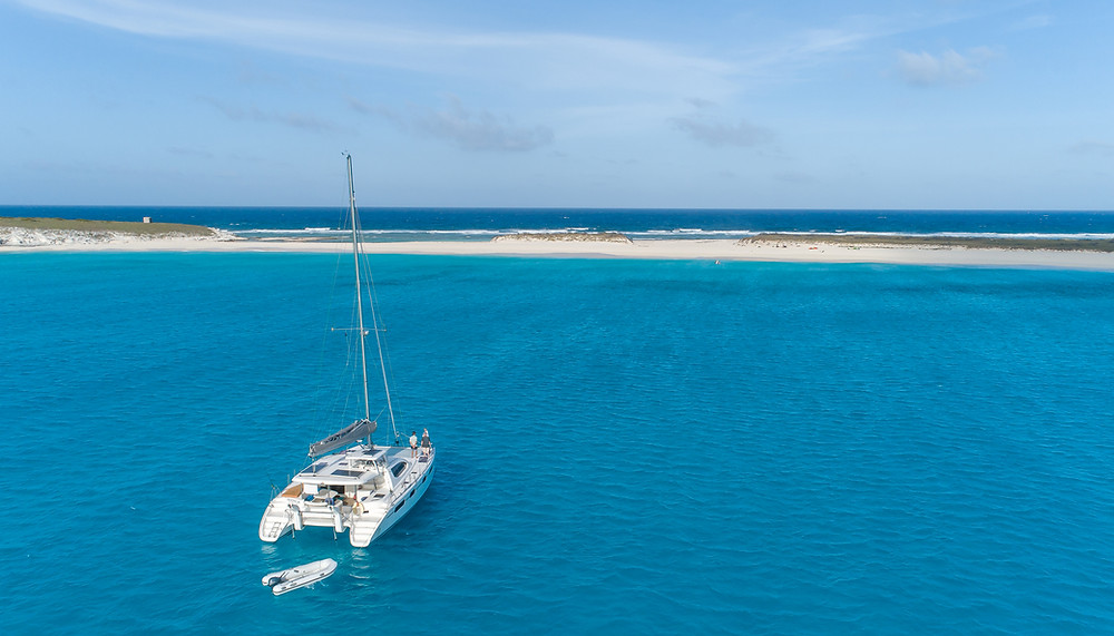 Catamaran at anchor by sandy island