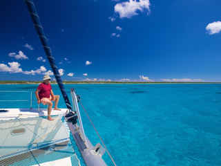 Man Sitting Bow Sailing Catamaran Turquoise Ocean Bahamas Charters