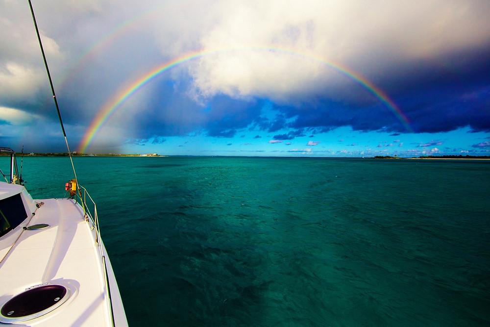Cataman on the ocean with double rainbow.