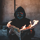 person-holding-a-burning-news-paper-clos