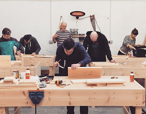a group of people being taught woodwork