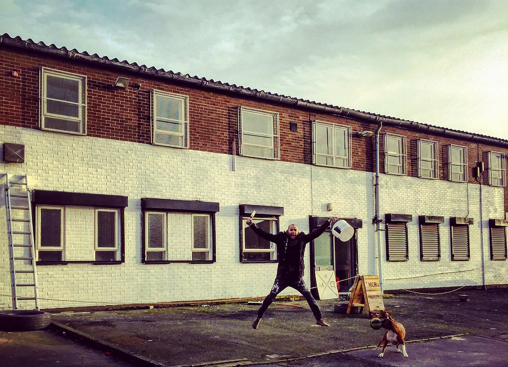 image of stephen hobson jumping in front of ne maker space in manchester