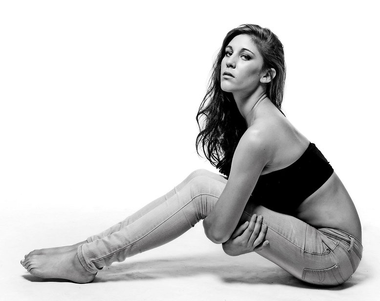 Girl sitting on the floor with arms roun legs
