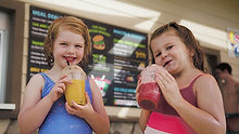 Two little girls sipping a freshly mad slushy from the concession stand
