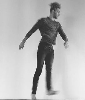 Elliot, a queer white person, jumping in a blur in a mottled sweater and jeans,