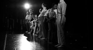 8 dancers standing in a line on a stage. The photo is taken from the side of the stage. The dancers are standing erect except some dancers who are contorted into body building poses. Each dancer wears high cut mens dress pants and button down shirts.
