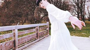 Elliot, a queer, white person, shown from the legs up in a sheer white dress. Their hair is trimmed in a black bowl cut and they are standing on a wooden bridge. They look down and off camera as they reach backward and tilt off center.