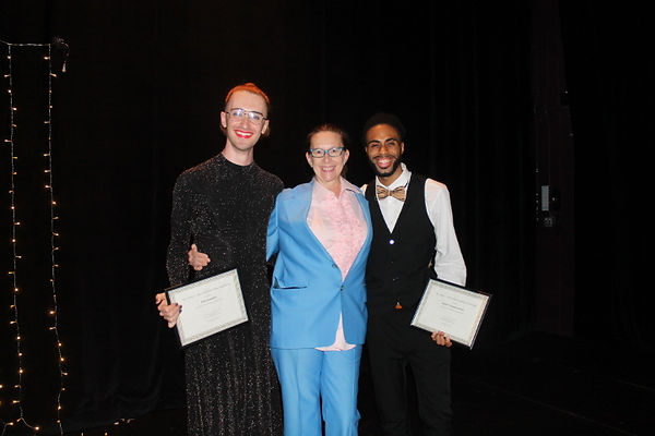 Elliot, a queer white person, in a glittery black dress, with their hair pulled back, glasses, and a bright red lip. Sara, a white woman in a vintage, powder blue tuxedo and blue spectacles. Danzel, a Black man in a black tuxedo with a gold bowtie. Elliot and Danzel hold certificates of an award they share. Sara has her arms around them both and all three are smiling