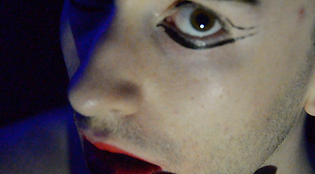 Elliot, a queer white person, in close up, staring directly at the camera, wearing poorly-applied eyeliner and some stubble
