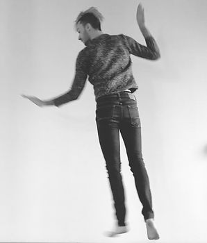 Elliot, a queer white person, jumping facing away from us mottled sweater and jeans,