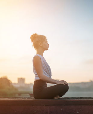 woman sitting in meditation pose, near a body of water at sunrise