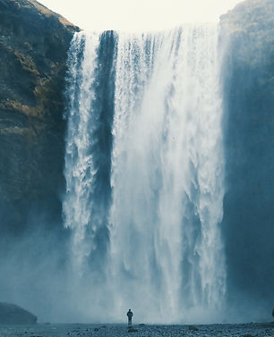 massive waterfall with human figure in foreground appearing very small by comparison