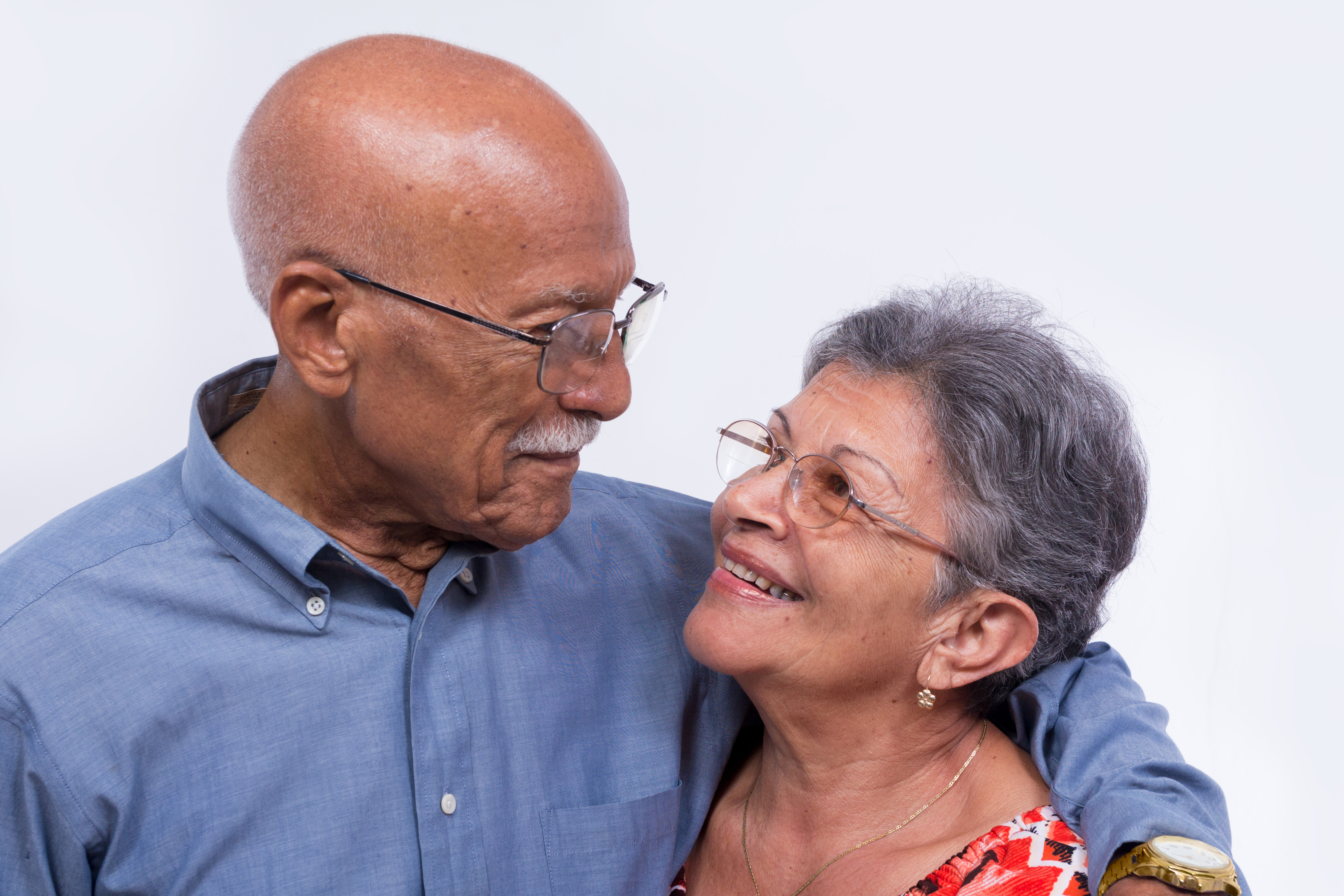 An smiling elderly couple, both wearing