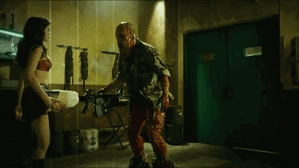 It's a scene from Grindhouse - Planet terror. Rose McGowan's Cherry has a gun attached to her leg. It's a movie by  Robert Rodriguez.