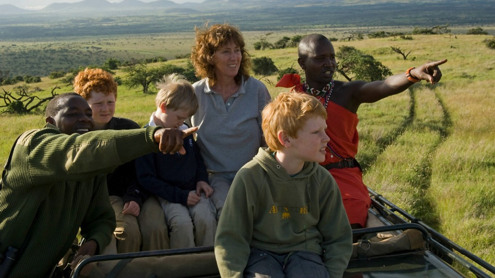 Kenya, Laikipia, Lewa Downs. A family on safari game viewing during a game drive at Lewa Downs. (MR)