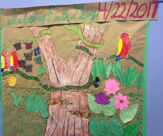 Paper and crayon art mural of tree, birds, and flowers