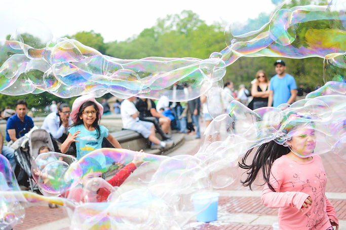 Children playing outside with big bubbles