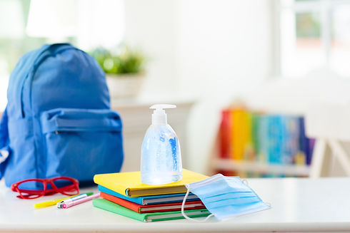 Backpack, glasses, pens, and hand sanitizer on a stack of books.