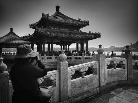 Tourists looking at Chinese architecture in black and white.