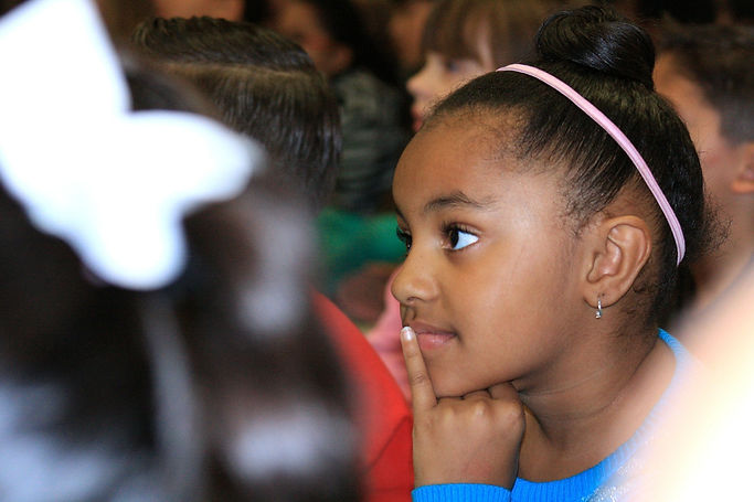 Young girl listening with finger on her mouth in auditorium