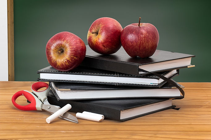 Stack of notebooks surrounded by scissors and chalk, with three apples on top.