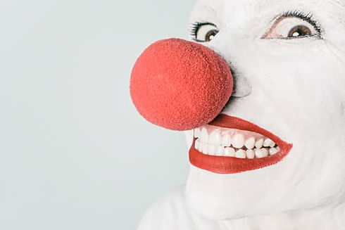 Close up of clown face with bright red ball on nose