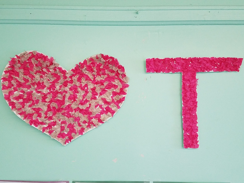 Art project of a Heart covered in pink and white crumpled tissue paper next to the letter T covered in pink crumped tissue paper.