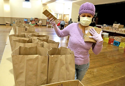 At the Filipino Community Center of Seattle, Lolita Lawson adds food items to be delivered