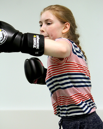 girl punching a bag in martial arts class