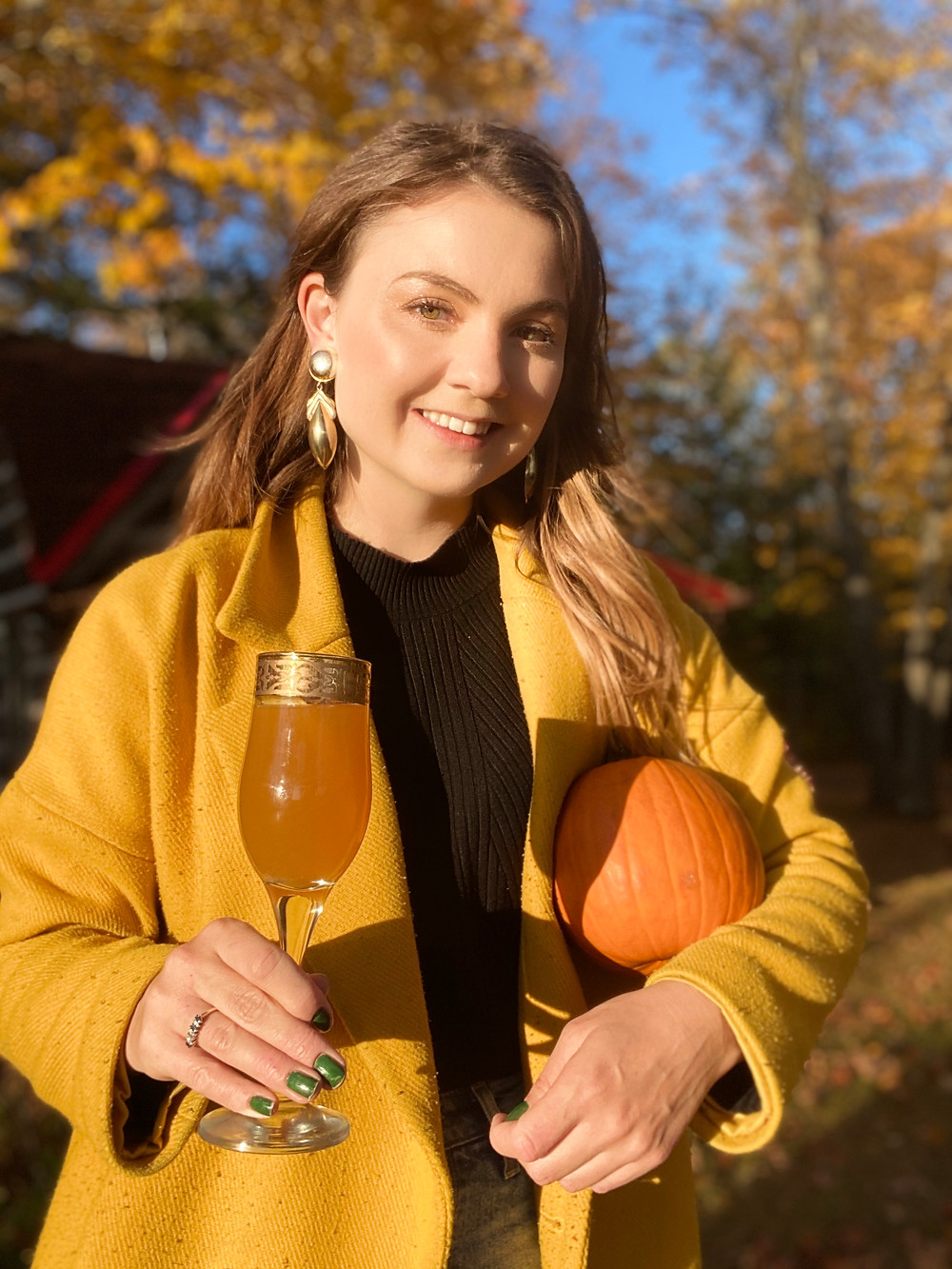 Rebecca standing amid autumn trees, holding her pumpkin spiced 75 cocktail and a pumpkin.