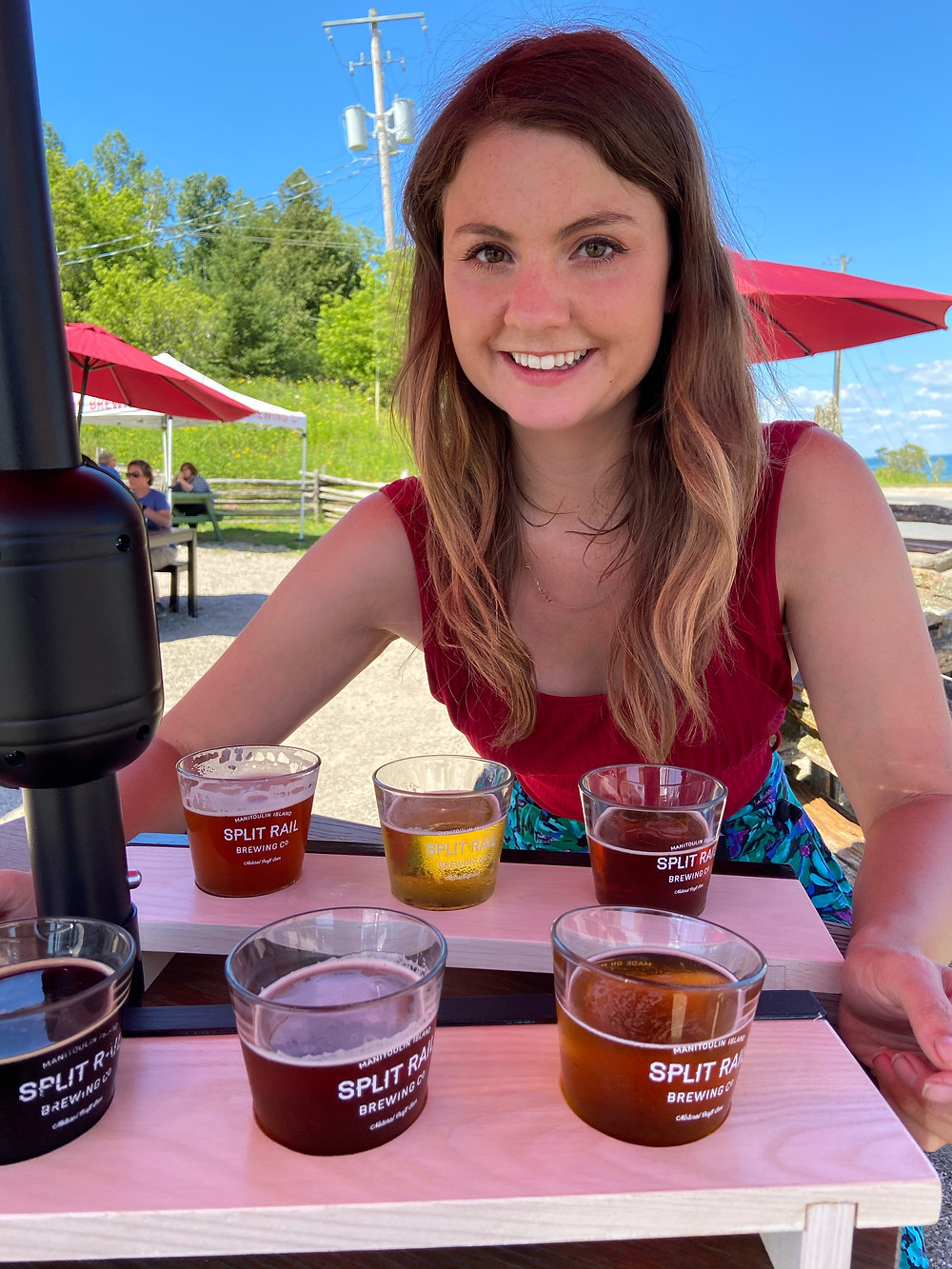 Rebecca smiling with a flight of beer at Split Rail Brewing Company, Manitoulin Islamd