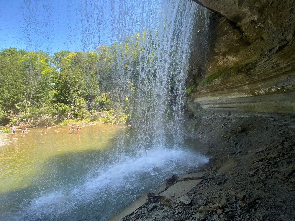An image taken behind a waterfall of a lagoon on Manitoulin Island