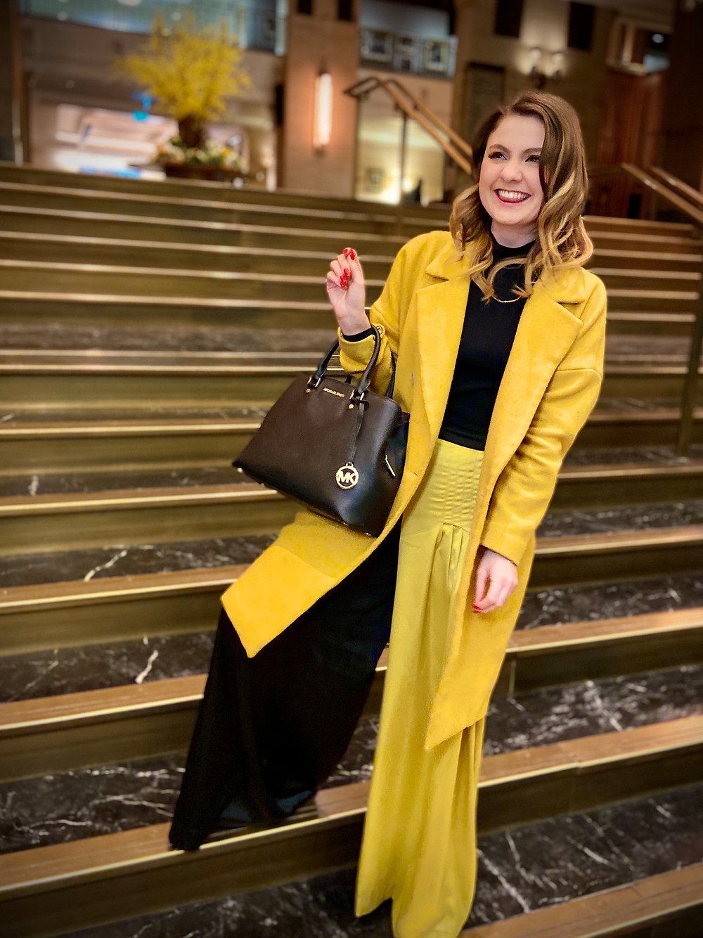 Rebecca wearing a fashionable yellow and black outfit, smiling and unaware of what is to come.