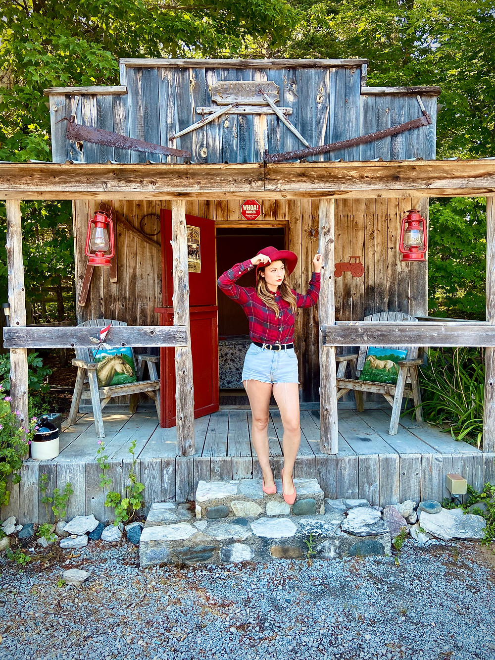Rebecca standing in a plaid shirt and blue jean shorts holding her hat and standing outside a cowboy style wooden building. She is on a ranch and there are horse decorations in sight.
