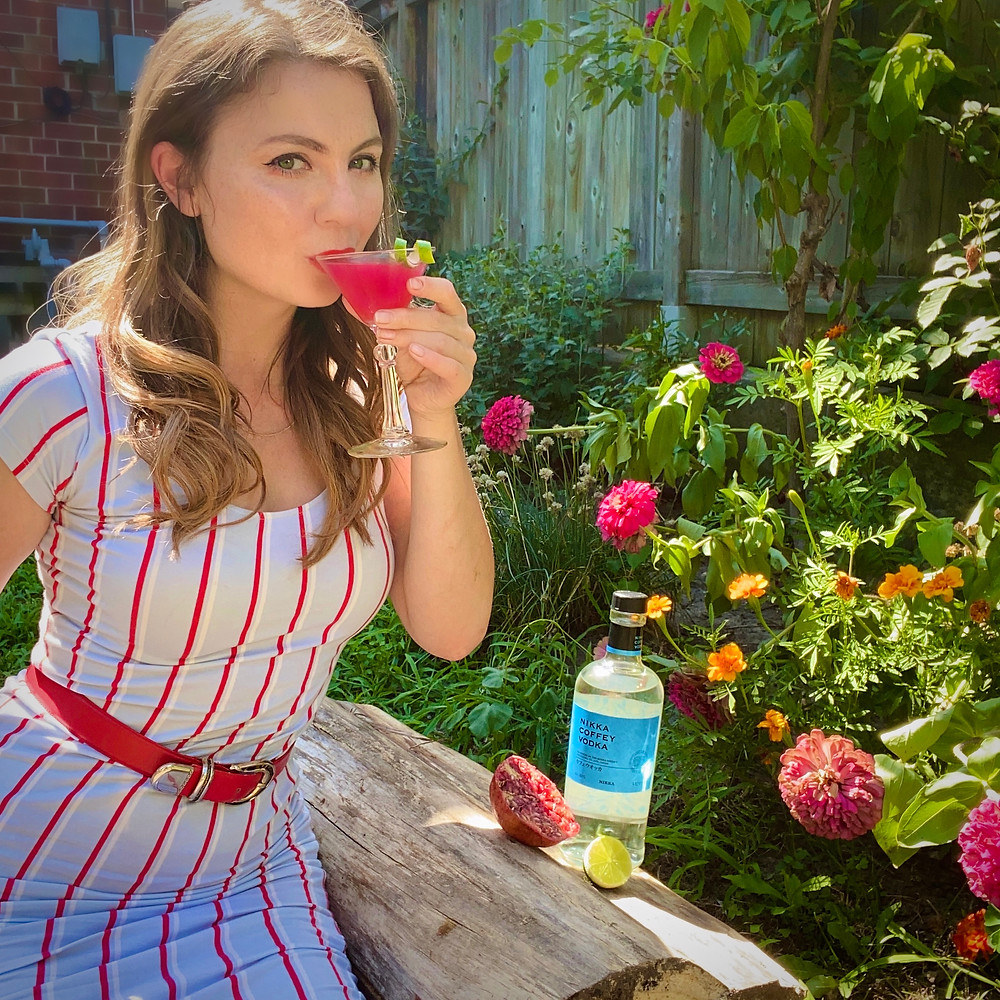 Rebecca wearing a blue and red dress sitting in a garden and drinking her pomegranate cosmo cocktail. If you ask her nicely, she might share the recipe!