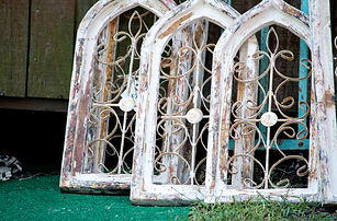 arched wooden windows at a salvage yard.