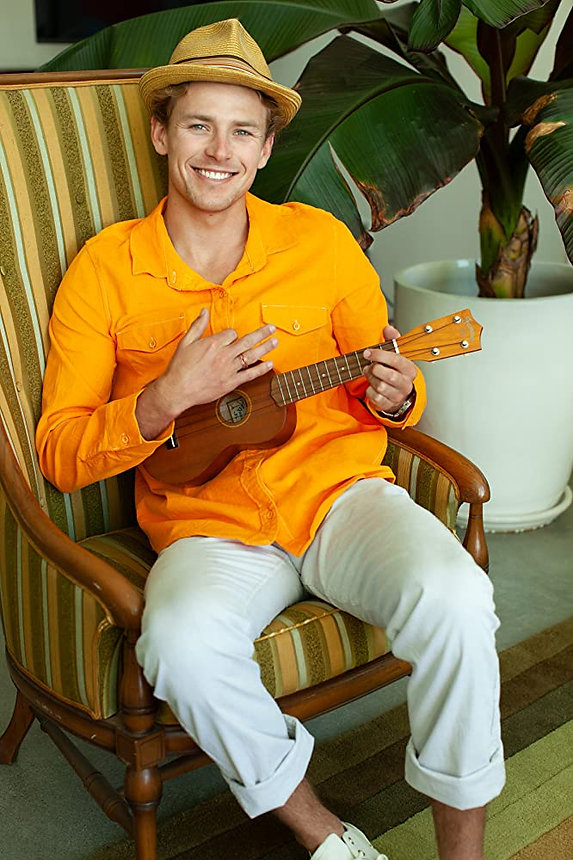 Sustainable Shane plays the ukelele and wears a fedora and yellow shirt in front of a palm.