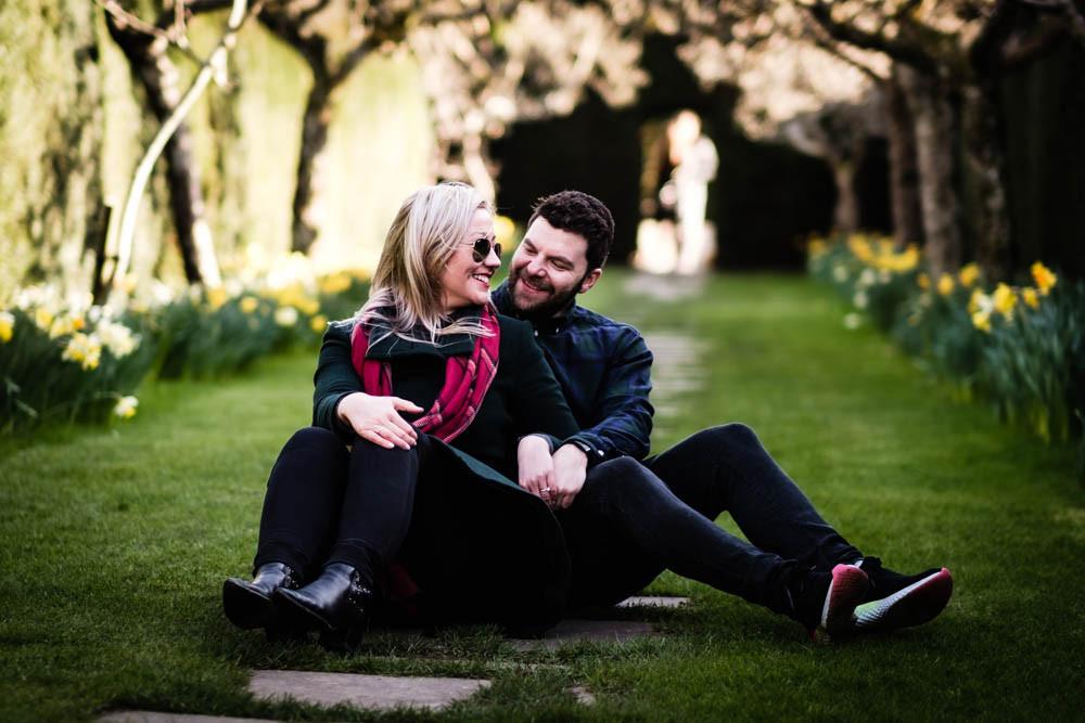 Young couple sitting amongst daffodils
